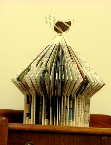 E. Talmage repurposes old books into paper sculptures, like this birdhouse from an old Audubon encyclopedia.