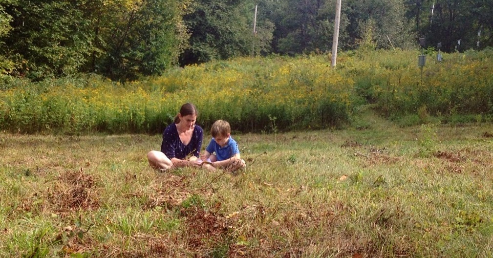 Kid in field with mom, investigating something small