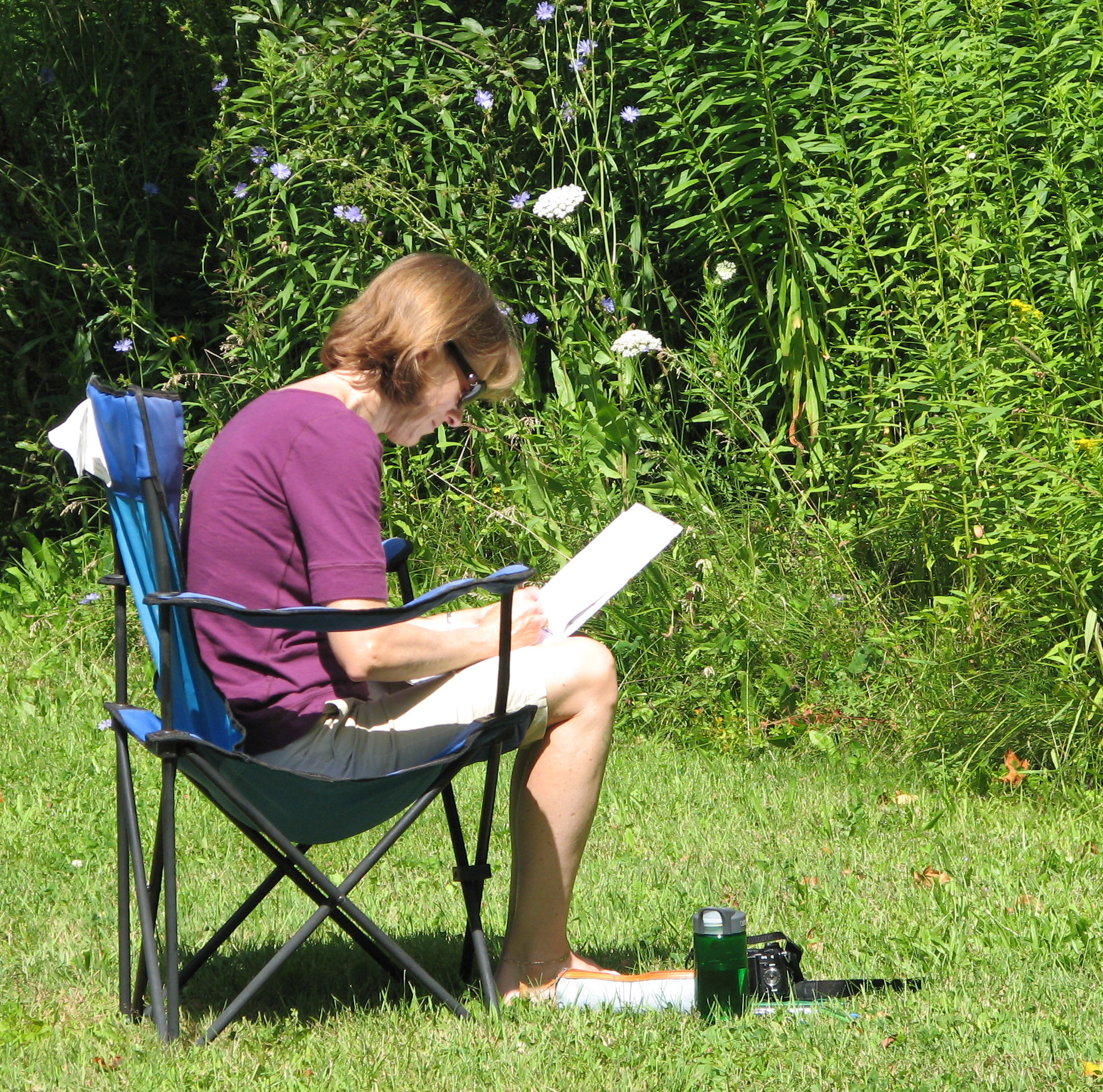 Person seated in camp chair own a lawn near blooing flowers, drawing or writing on large pad pof paper.
