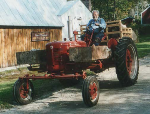 Bob Spear driving a red tractor at the Birds of Vermont Museum