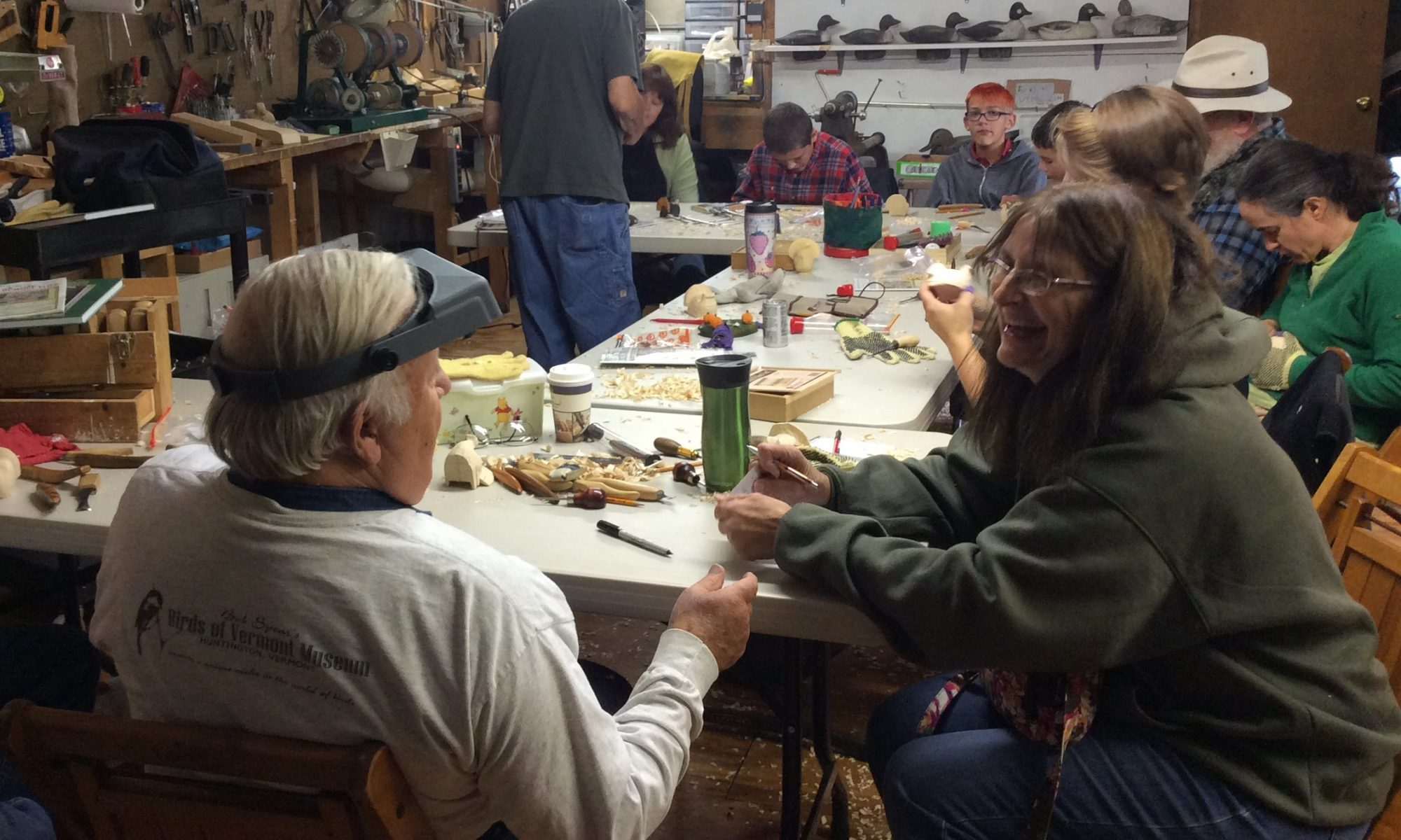 Several woodcarvers carving, painting, and chatting at tables in the workshop at the Birds of Vermont Museum.