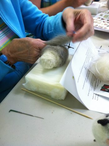making a felted owl: Work In Process 2 (wrapping soft gray wool around wool body; work is on a plastic-protect foam pad to protect needles and work surface)